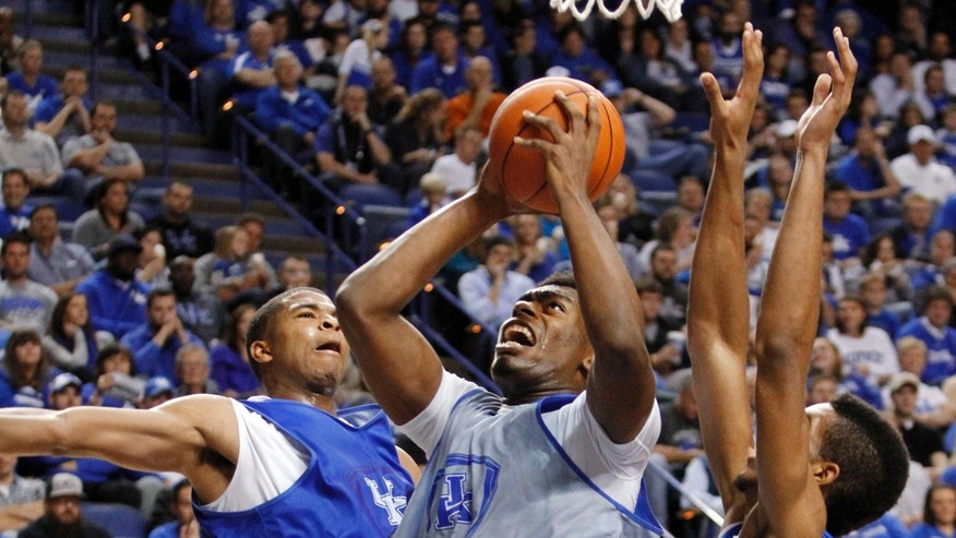 White team's Dakari Johnson, middle, shoots between Blue team's Aaron Harrison, left, and Marcus Lee during Kentucky's NCAA college basketball scrimmage, Tuesday, Oct. 29, 2013, in Lexington, Ky. The Blue team won 99-71. (AP Photo/James Crisp)