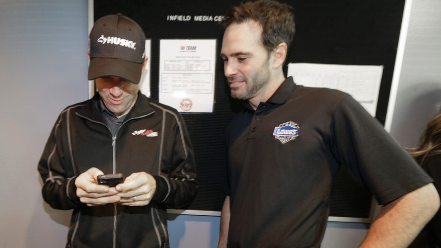 NASCAR Sprint Cup Series driver Matt Kenseth, left, shows fellow driver Jimmie Johnson something on his smart phone between news conferences in the media center at Texas Motor Speedway in Fort Worth, Texas, Friday, Nov. 1, 2013.  (AP Photo/LM Otero)