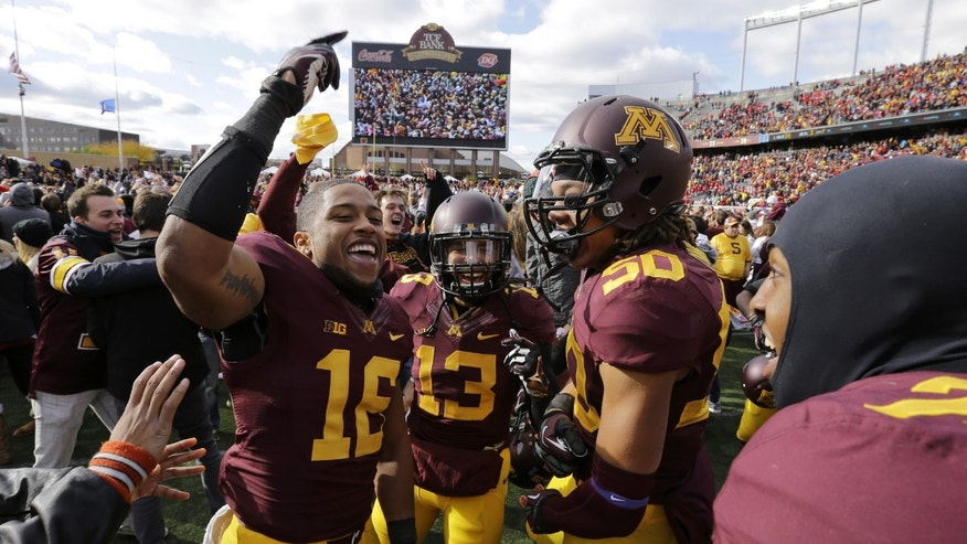 Minnesota wide receiver Jamel Harbison (16) celebrates with teammates and fans after Minnesota beat Nebraska 34-23 in an NCAA college football game in Minneapolis Saturday, Oct. 26, 2013. (AP Photo/Ann Heisenfelt)