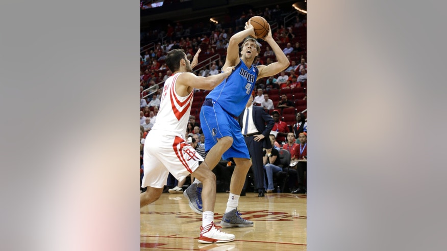 Dallas Mavericks' Dirk Nowitzki (41) takes an off-balance shot under pressure from Houston Rockets' Omri Casspi, left, in the first half of an NBA basketball game Friday, Nov. 1, 2013, in Houston. (AP Photo/Pat Sullivan)