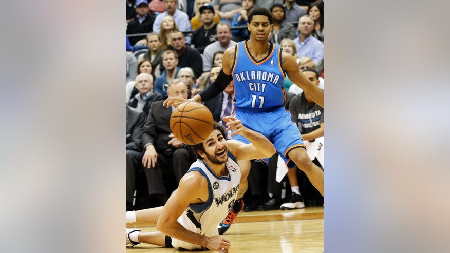 Minnesota Timberwolves' Ricky Rubio, bottom, of Spain, reaches in vain for the loose ball as Oklahoma City Thunder's Jeremy Lamb watches in the second half of an NBA basketball game, Friday, Nov. 1, 2013, in Minneapolis. The Timberwolves won 100-81. (AP Photo/Jim Mone)