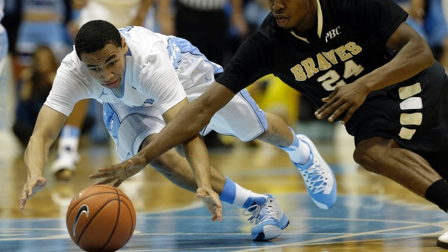 North Carolina's Marcus Paige, left, and UNC Pembroke's Jihad Wright dive for a loose ball during the first half of an exhibition NCAA college basketball game in Chapel Hill, N.C., Friday, Nov. 1, 2013. (AP Photo/Gerry Broome)