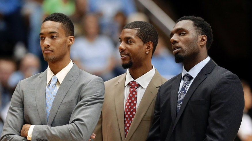 North Carolina's J.P. Tokoto, left, Leslie McDonald, center, and P.J. Hairston watch during warmups prior to an exhibition NCAA college basketball game against UNC Pembroke in Chapel Hill, N.C., Friday, Nov. 1, 2013. The athletes did not compete in tonight's game due to eligibility issues. (AP Photo/Gerry Broome)