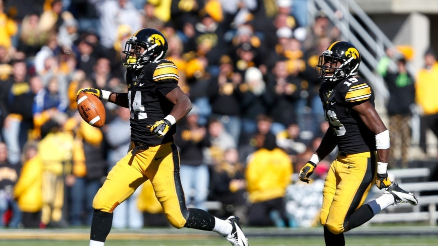 Iowa defensive backs Desmond King (14) and B.J. Lowery (19) celebrate after King's recovery of a fumble by Northwestern running back Mike Trumpy (32) during the fourth quarter of an  NCAA college football game Saturday, Oct. 26, 2013 at Kinnick Stadium in Iowa City, Iowa.  (AP Photo/Brian Ray)