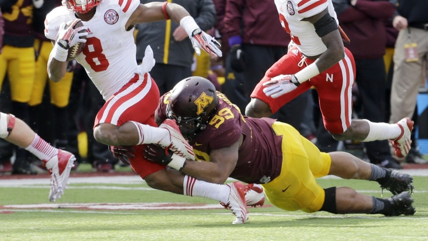 Minnesota defensive lineman Ra'Shede Hageman (99) tackles Nebraska running back Ameer Abdullah (8) on a 6-yard gain during the second quarter of an NCAA college football game in Minneapolis Saturday, Oct. 26, 2013. Minnesota beat Nebraska 34-23. (AP Photo/Ann Heisenfelt)