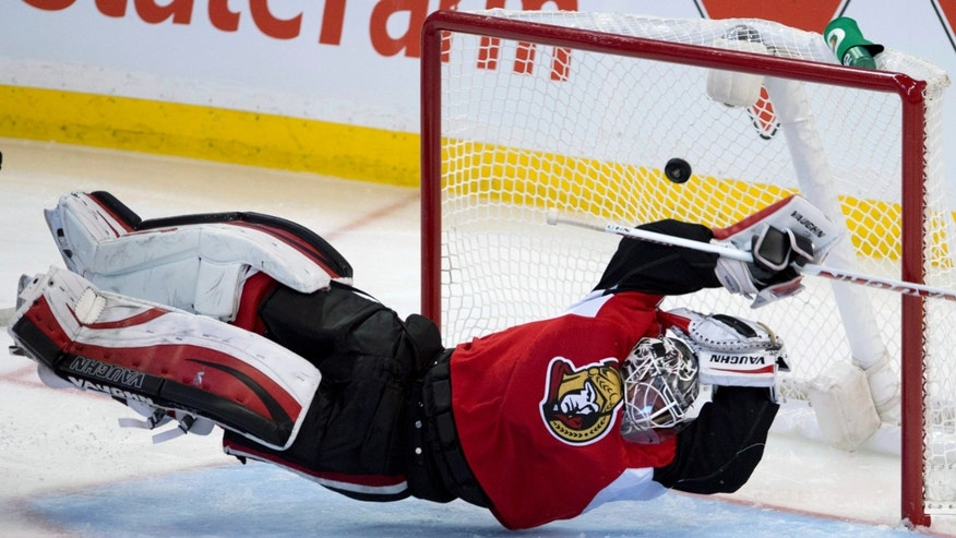 Ottawa Senators goalie Robin Lehner dives for the puck as the New York Islanders score on a shot from Frans Nielsen during the third period of an NHL hockey game Friday, Nov. 1, 2013, in Calgary, Alberta. (AP Photo/The Canadian Press, Larry MacDougal)