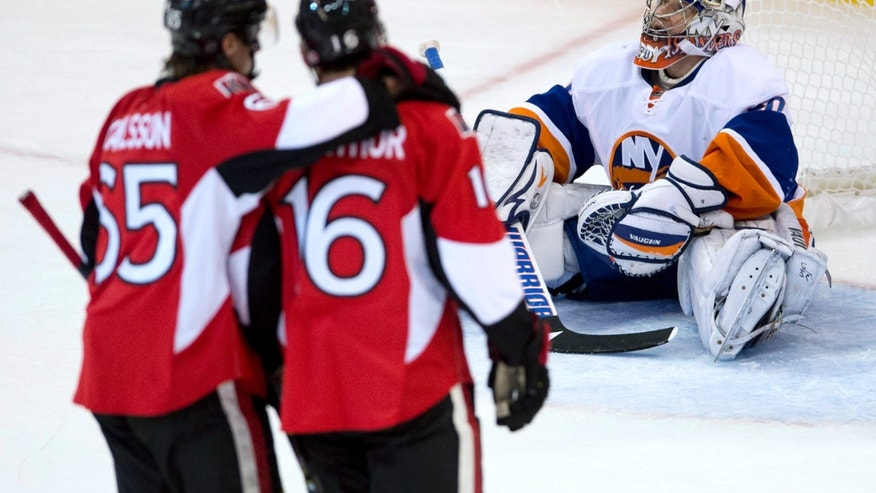 New York Islanders goalie Evgeni Nabokov sits in the crease as Ottawa Senators defenseman Erik Karlsson, left, congratulates Clarke MacArthur on his goal during the second period of an NHL hockey game Friday, Nov. 1, 2013, in Ottawa, Ontario. (AP Photo/The Canadian Press, Adrian Wyld)