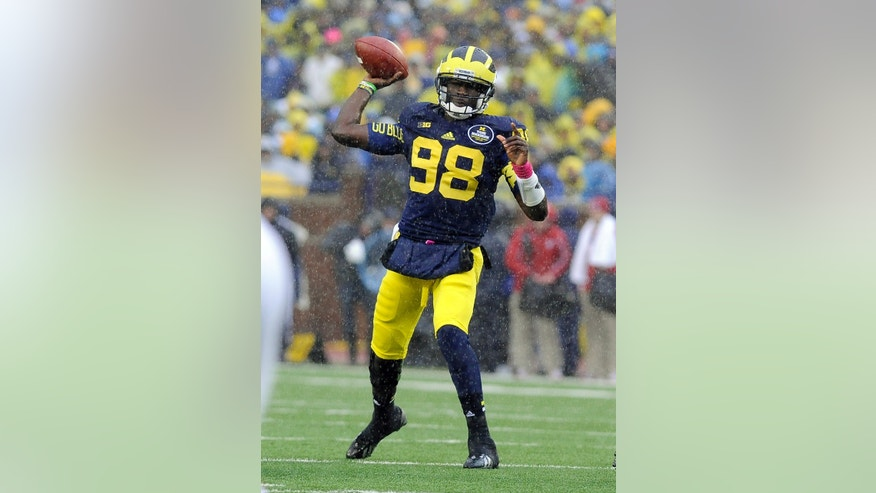 FILE - In this Oct. 19, 2013 file photo, Michigan quarterback Devin Gardner throws a pass in the rain during an NCAA college football game against Indiana in Ann Arbor, Mich. Heading into the final month of regular season Michigan is battling for supremacy in the  Big Ten's Legends Division with Michigan  State and Nebraska. (AP Photo/Lon Horwedel, File)