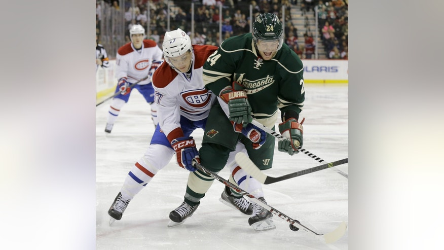 Montreal Canadiens center Alex Galchenyuk (27) and Minnesota Wild left wing Matt Cooke (24) battle for the puck during the second period of an NHL hockey game in St. Paul, Minn., Friday, Nov. 1, 2013. (AP Photo/Ann Heisenfelt)