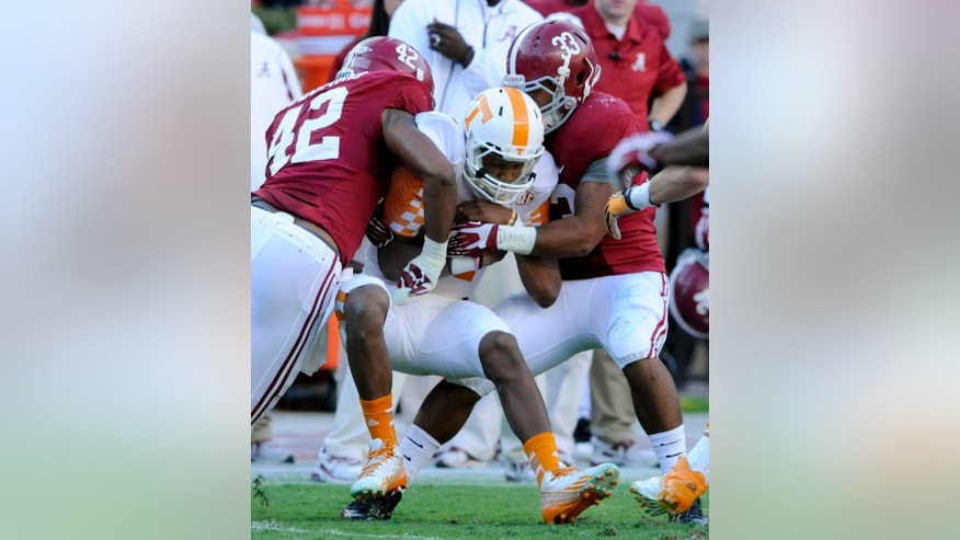 In this Oct. 26, 2013, photo, Tennessee quarterback Josh Dobbs is tackled by Alabama defenders Adrian Hubbard, left, and Trey DePriest during a NCAA football game in Tuscaloosa, Ala. (AP Photo/Michael Patrick, Knoxville News Sentinel)