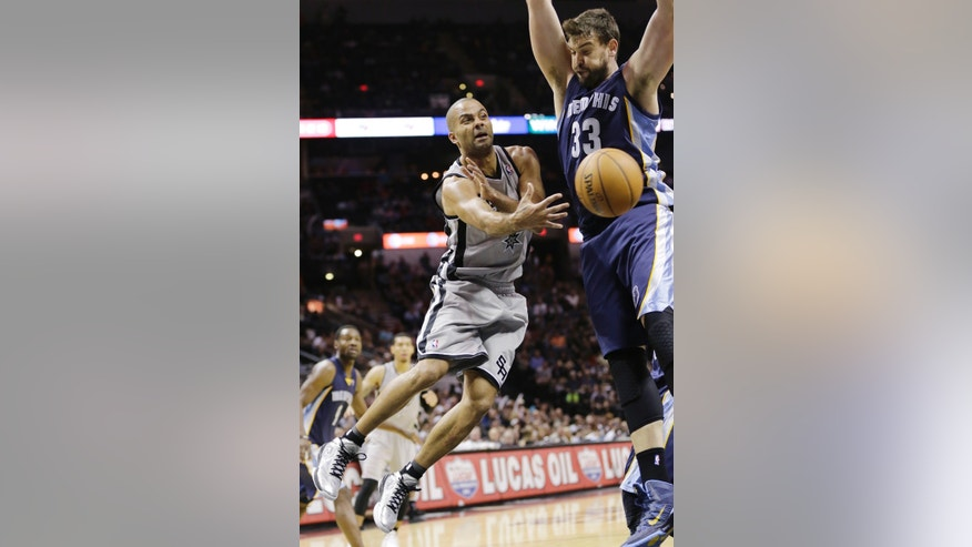 San Antonio Spurs' Tony Parker (9), of France, passes the ball around Memphis Grizzlies' Marc Gasol (33), of Spain, during the second half on an NBA basketball game, Wednesday, Oct. 30, 2013, in San Antonio. (AP Photo/Eric Gay)