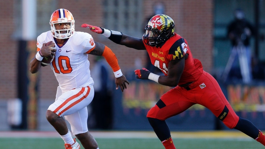 Clemson quarterback Tajh Boyd (10) tries to outrun Maryland linebacker Marcus Whitfield in the first half of an NCAA college football game in College Park, Md., Saturday, Oct. 26, 2013. (AP Photo/Patrick Semansky)