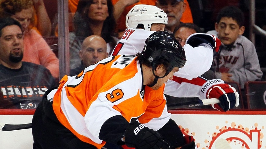 Philadelphia Flyers' Steve Downie, front, checks Washington Capital's  Steve Olesky into the board during the first period of an NHL hockey game, Friday, Nov. 1, 2013, in Philadelphia. Downie, a former Flyer, was acquired on Oct. 31 in a trade with the Colorado Avalanche for Maxime Talbot. (AP Photo/Tom Mihalek)