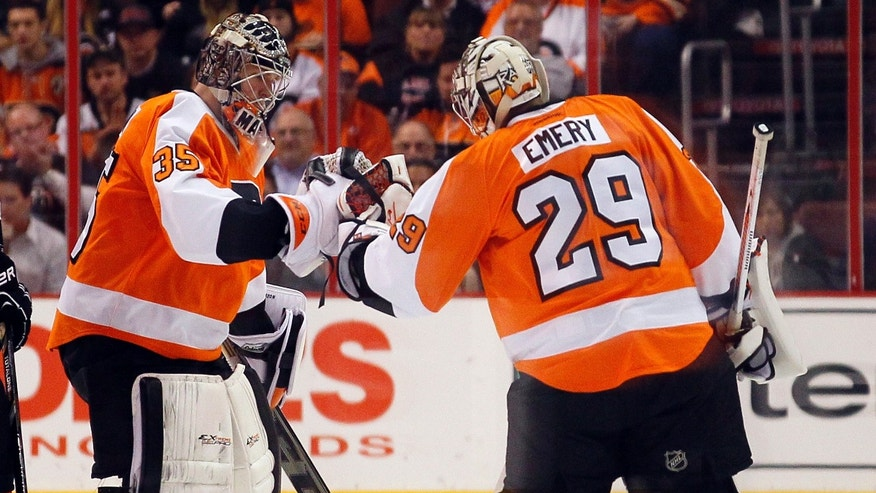 Philadelphia Flyers goalie Steve Mason, left, taps gloves with Ray Emery as he leaves the game in the second period of an NHL hockey game with the Washington Capitals, Friday, Nov. 1, 2013, in Philadelphia. Mason gave up three goals before being pulled mid-way through the period. (AP Photo/Tom Mihalek)