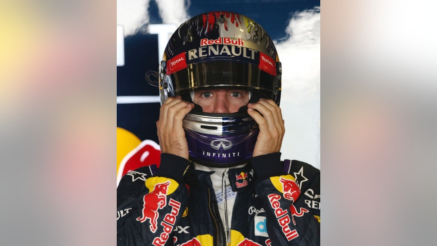 Red Bull driver Sebastian Vettel of Germany adjusts his helmet at pits during the first free practice at the Yas Marina racetrack in Abu Dhabi, United Arab Emirates, Friday, Nov. 1, 2013. The Emirates Formula One Grand Prix will take place on Sunday. (AP Photo/Luca Bruno)