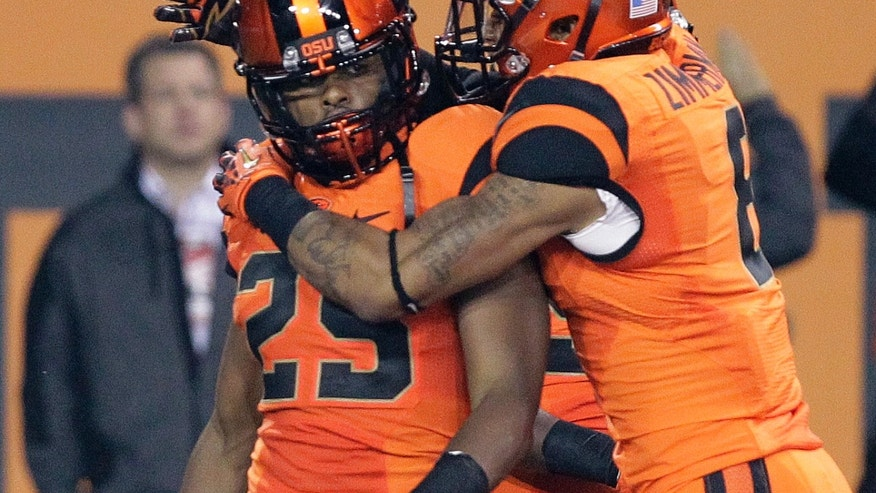 Oregon State defender Ryan Murphy is congratulated by teammate Tyrequek Zimmerman after Murphy scored on an interception during the first half of an NCAA college football game against Southern California in Corvallis, Ore., Friday, Nov. 1, 2013. (AP Photo/Don Ryan)