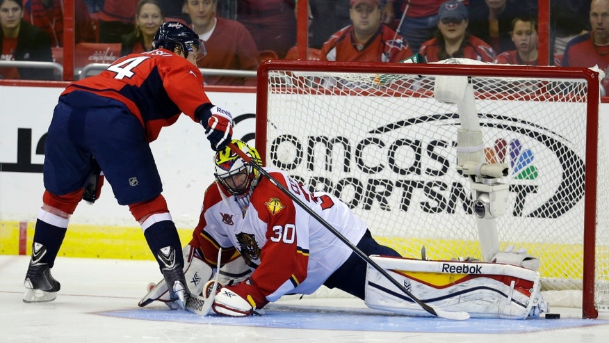 Washington Capitals center Mikhail Grabovski (84), from Germany, scores past the skate of Florida Panthers goalie Scott Clemmensen (30) in the shootout of an NHL hockey game, Saturday, Nov. 2, 2013, in Washington. The Capitals won 3-2. (AP Photo/Alex Brandon)