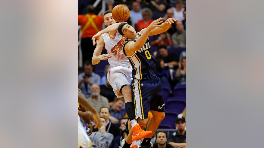 Phoenix Suns center Miles Plumlee, left, knocks the ball away from Utah Jazz center Enes Kanter during the first half of an NBA basketball game Friday, Nov. 1, 2013, in Phoenix. (AP Photo/Matt York)