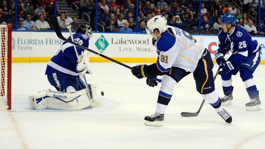 Tampa Bay Lightning defenseman Matthew Carle, right, looks on as Lightning goalie Ben Bishop, left, defends the goal from a shot by St. Louis Blues right wing Vladimir Tarasenko, of Russia, during the first period of an NHL hockey game Saturday, Nov. 2, 2013, in Tampa, Fla. (AP Photo/Brian Blanco)