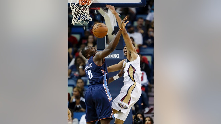 New Orleans Pelicans forward Anthony Davis, right, vies for a loose ball against Charlotte Bobcats forward Bismack Biyombo (0) in the first half of an NBA basketball game in New Orleans, Saturday, Nov. 2, 2013. (AP Photo/Gerald Herbert)