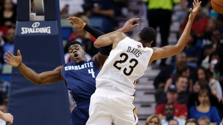 New Orleans Pelicans forward Anthony Davis (23) is fouled by Charlotte Bobcats forward Jeff Adrien (4) in the first half of an NBA basketball game in New Orleans, Saturday, Nov. 2, 2013. (AP Photo/Gerald Herbert)
