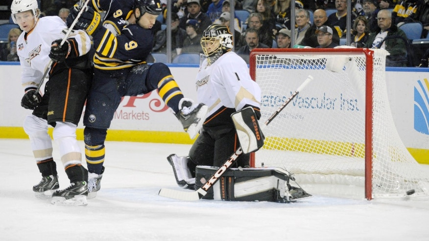 Anaheim Ducks defenseman Hampus Lindholm, left, of Sweden, tangles with Buffalo Sabres center Steve Ott, center, as he deflects a shot wide of Ducks' goaltender Jonas Hiller, right, of the Czech Republic during the first period of an NHL hockey game in Buffalo, N.Y., Saturday, Nov. 2, 2013. (AP Photo/Gary Wiepert)