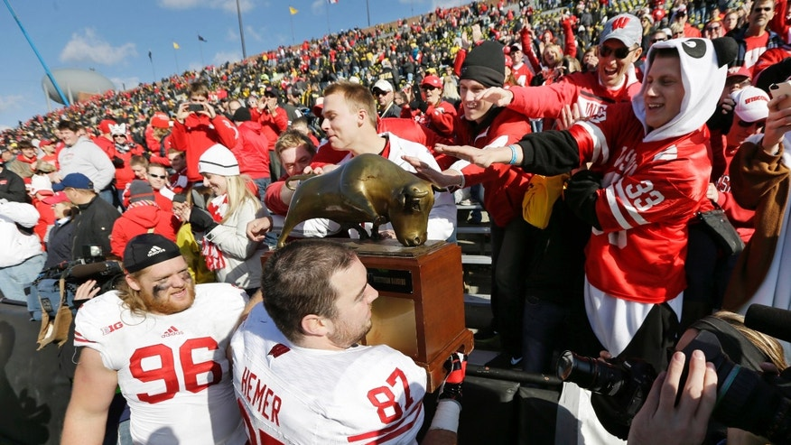 Wisconsin defensive end Ethan Hemer celebrates with fans as he carries the Heartland trophy off the field after their 28-9 victory over Iowa in an NCAA college football game, Saturday, Nov. 2, 2013, in Iowa City, Iowa. (AP Photo/Charlie Neibergall)