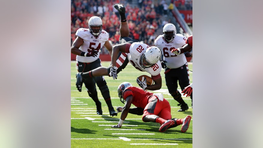 Temple running back Kenneth Harper (20) dives for yardage over Rutgers defensive back Tejay Johnson (9) during the first half of an NCAA college football game in Piscataway, N.J., Saturday, Nov. 2, 2013. (AP Photo/Mel Evans)