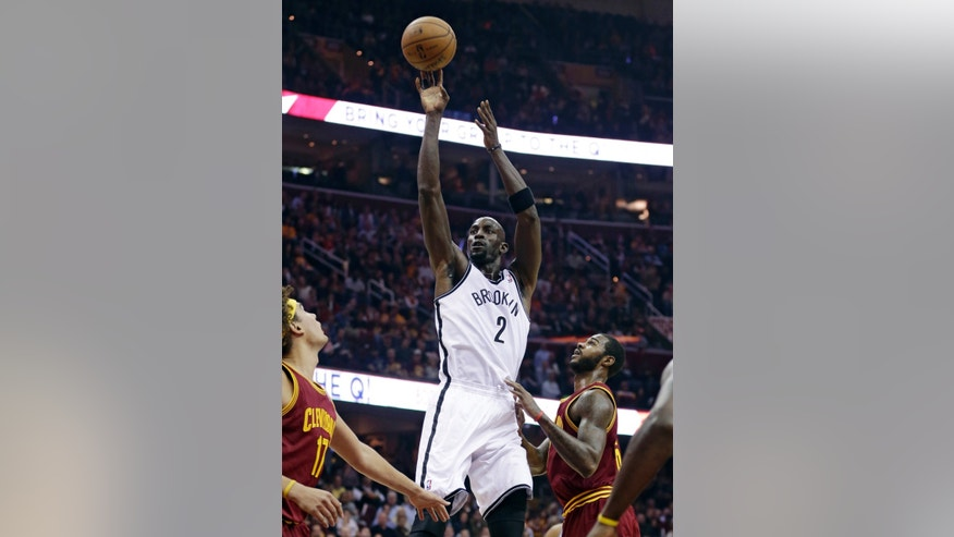 Brooklyn Nets' Kevin Garnett , center, shoots over Cleveland Cavaliers' Anderson Varejao, left, of Brazil, and Earl Clark during the first quarter of an NBA basketball game Wednesday, Oct. 30, 2013, in Cleveland. (AP Photo/Tony Dejak)