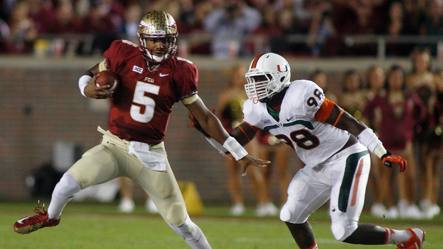 Florida State quarterback Jameis Winston (5) sidesteps a tackle attempt by Miami defensive end Al-Quadin Muhammad (98) during the second quarter of an NCAA college football game Saturday, Nov. 2, 2013, in Tallahassee, Fla. (AP Photo/Phil Sears)
