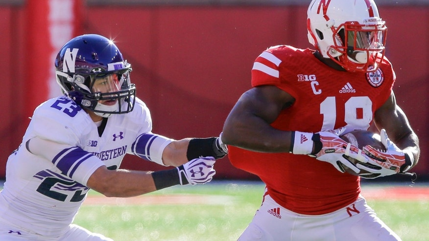 Northwestern centerback Nick VanHoose (23) hangs on to the shirt of Nebraska wide receiver Quincy Enunwa (18), in the first half of an NCAA college football game in Lincoln, Neb., Saturday, Nov. 2, 2013. (AP Photo/Nati Harnik)