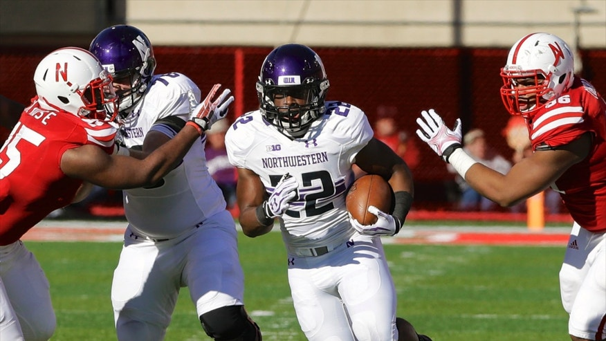 Northwestern running back Treyvon Green (22) carries the ball through a gap between Nebraska linebacker Michael Rose (15) and Nebraska defensive tackle Aaron Curry (96), in the first half of an NCAA college football game in Lincoln, Neb., Saturday, Nov. 2, 2013. (AP Photo/Nati Harnik)