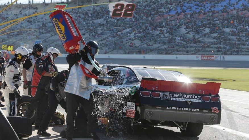 The pit crew finishes fueling Brad Keselowski's car during the NASCAR Nationwide Series auto race at Texas Motor Speedway in Fort Worth, Texas, Saturday, Nov. 2, 2013. (AP Photo/Brandon Wade)