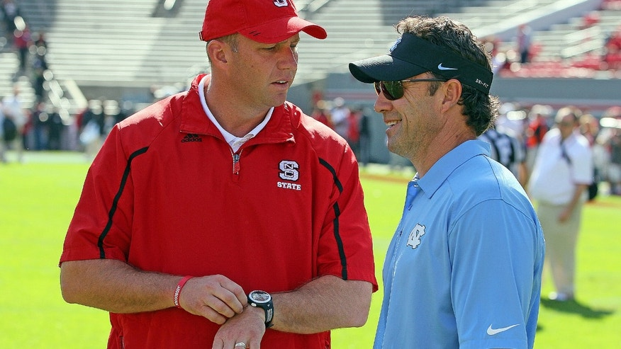 North Carolina State head coach Dave Doeren, left, speaks with North Carolina head coach Larry Fedora prior to the start of their NCAA college football game in Raleigh , N.C., Saturday, Nov. 2, 2013. (AP Photo/Karl B DeBlaker)