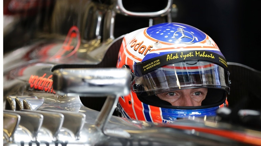 McLaren Mercedes driver Jenson Button of Britain watches at pits during the third free practice at the Yas Marina racetrack in Abu Dhabi, United Arab Emirates, Saturday, Nov. 2, 2013. The Emirates Formula One Grand Prix will take place on Sunday. (AP Photo/Hassan Ammar)