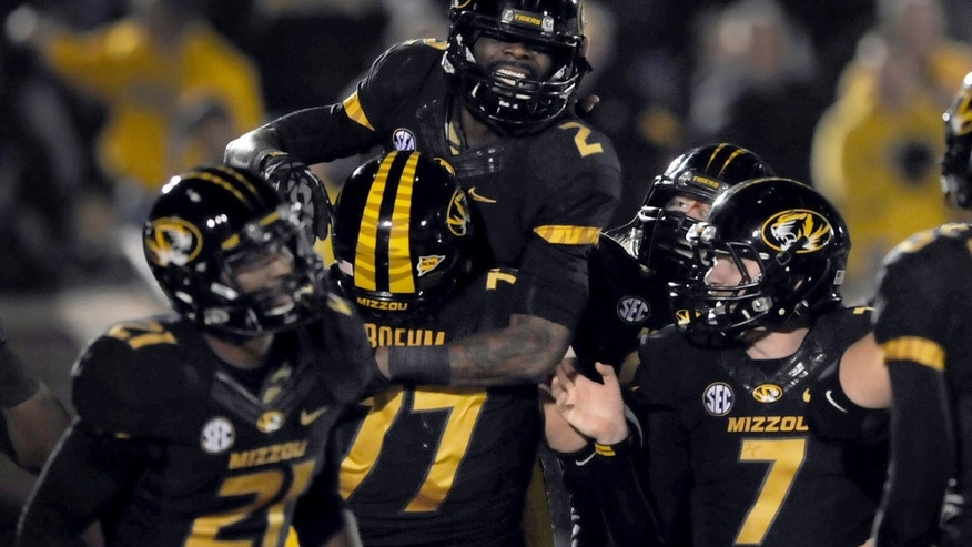 Missouri wide receiver L'Damian Washington (2) is congratulated by teammates including Bud Sasser (21), Evan Boehm (77) and Maty Mauk (7) after catching a touchdown pass during the first half of an NCAA college football game against Tennessee, Saturday, Nov. 2, 2013, in Columbia, Mo. (AP Photo/L.G. Patterson)