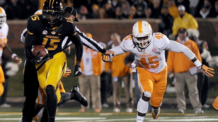 Missouri wide receiver Dorial Green-Beckham, left, runs past Tennessee linebacker A.J. Johnson after catching a 9-yard pass and running it in for a touchdown during the first half of an NCAA college football game Saturday, Nov. 2, 2013, in Columbia, Mo. (AP Photo/L.G. Patterson)