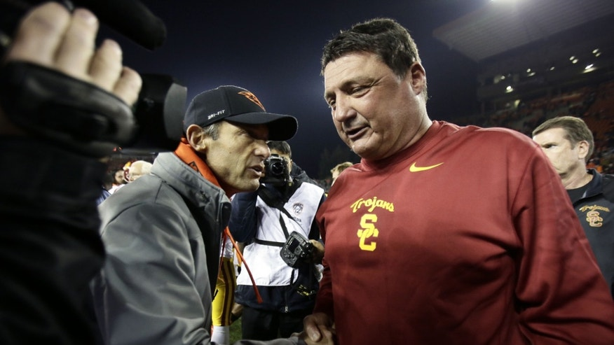 Southern California interim football coach Ed Orgeron, right, shakes hands with Oregon State coach Mike Riley after their NCAA college football game in Corvallis, Ore., Friday, Nov. 1, 2013. USC won 31-14. (AP Photo/Don Ryan)