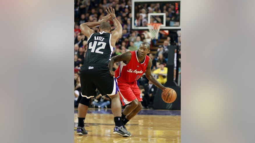 Los Angeles Clippers guard Jamal Crawford, right, dribbles past Sacramento Kings forward Chuck Hayes during the first quarter of an NBA basketball game in Sacramento, Calif., Friday, Nov. 1, 2013. (AP Photo/Rich Pedroncelli)