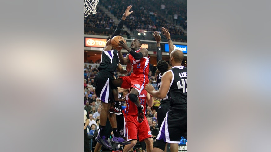 Los Angeles Clippers guard Darren Collison, center, drives to the basket against Sacramento Kings forward Jason Thompson, left, during the first quarter of an NBA basketball game in Sacramento, Calif., Friday, Nov. 1, 2013. (AP Photo/Rich Pedroncelli)