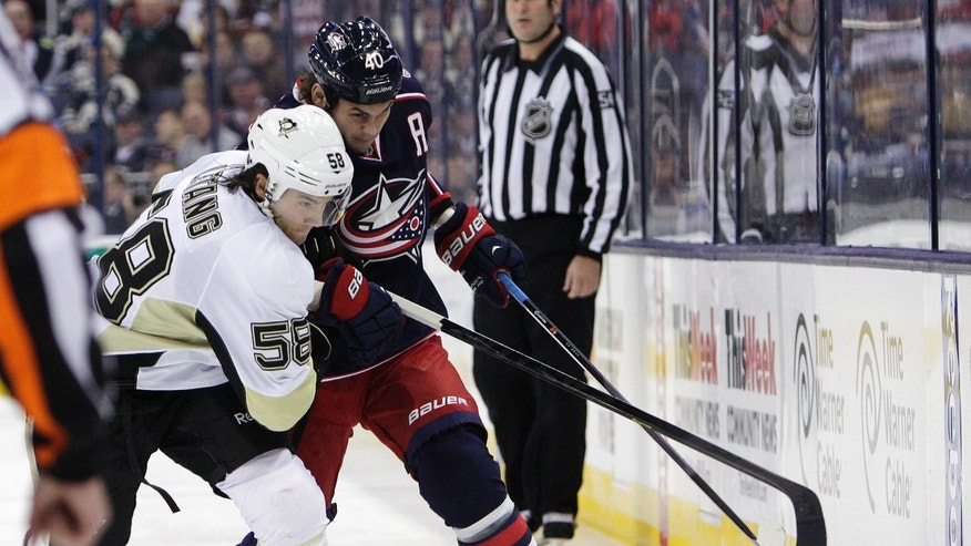 Pittsburgh Penguins' Kris Letang, left, and Columbus Blue Jackets' Jared Boll chase a loose puck during the second period of an NHL hockey game Saturday, Nov. 2, 2013, in Columbus, Ohio. (AP Photo/Jay LaPrete)