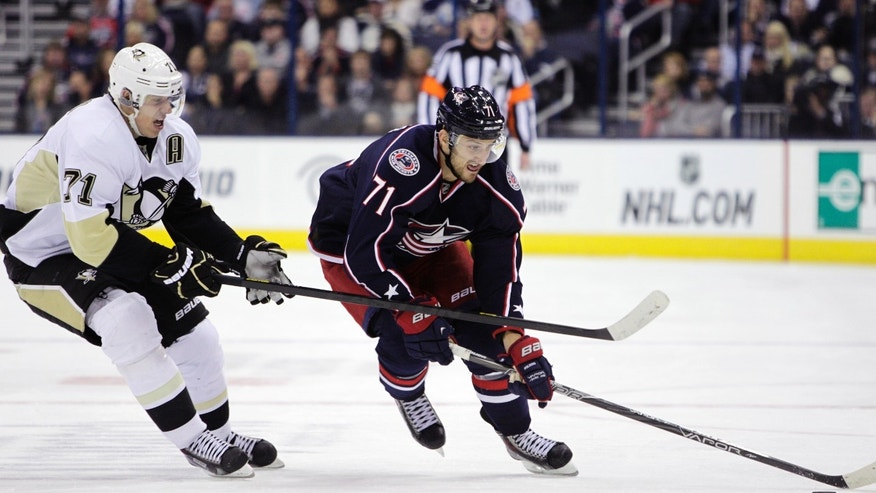 Columbus Blue Jackets' Nick Foligno, right, carries the puck across the blue line as Pittsburgh Penguins' Evgeni Malkin, of Russia, defends during the second period of an NHL hockey game Saturday, Nov. 2, 2013, in Columbus, Ohio. (AP Photo/Jay LaPrete)