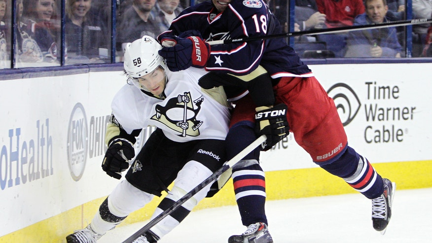 Pittsburgh Penguins' Kris Letang, left, and Columbus Blue Jackets' RJ Umberger fight for a loose puck during the second period of an NHL hockey game Saturday, Nov. 2, 2013, in Columbus, Ohio. (AP Photo/Jay LaPrete)