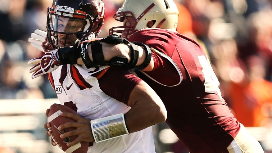 Virginia Tech quarterback Logan Thomas, left, is sacked by Boston College's Steele Divitto during the first half of a college football game at Alumni Stadium in Boston, Saturday, Nov. 2, 2013. (AP Photo/Winslow Townson)