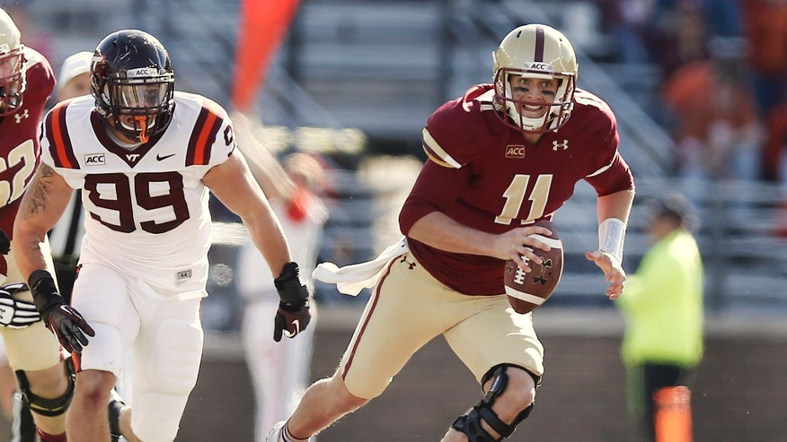 Boston College quarterback Chase Rettig scrambles away from Virginia Tech's James Gayle (99) during the first half of a college football game at Alumni Stadium in Boston, Saturday, Nov. 2, 2013. (AP Photo/Winslow Townson)