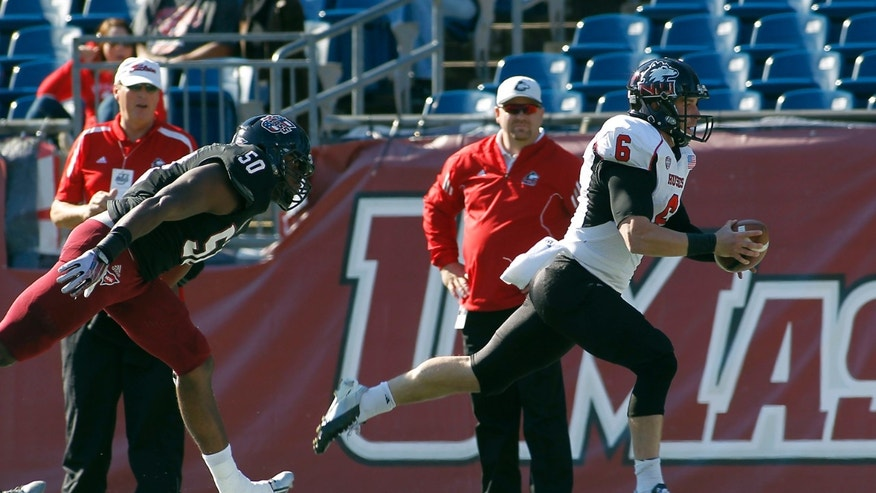 Northern Illinois quarterback Jordan Lynch (6) runs for a touchdown past Massachusetts defensive lineman Justin Anderson (50) during the first half of an NCAA football game in Foxborough, Mass., Saturday, Nov. 2, 2013. (AP Photo/Stew Milne)