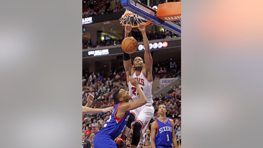 Chicago Bulls' Taj Gibson (22) scores over Philadelphia 76ers' Evan Turner in the first half of an NBA basketball game Saturday, Nov. 2, 2013, in Philadelphia.  (AP Photo/H. Rumph Jr)