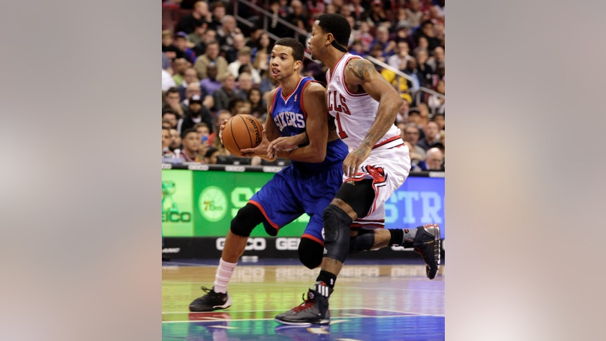 Chicago Bulls' Derrick Rose, right, defends as Philadelphia 76ers' Michael Carter-Williams drives onto the lane in the first half of an NBA basketball game Saturday, Nov. 2, 2013, in Philadelphia. (AP Photo/H. Rumph Jr)