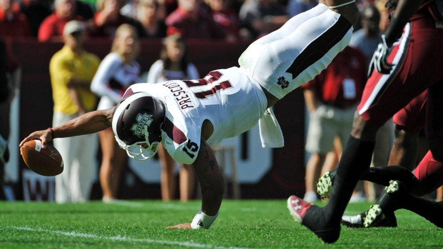 Mississippi State quarterback Dak Prescott (15) dives for the goal line during the first half of an NCAA college football game against South Carolina, Saturday, Nov. 2, 2013, in Columbia, S.C. Prescott did not score on the play. (AP Photo/Rainier Ehrhardt)