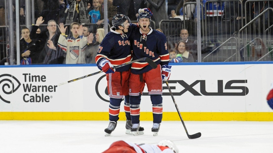 New York Rangers' Derek Stepan, right, celebrates with Ryan McDonagh, left, after Stepan scored a goal, as Carolina Hurricanes' Alexander Semin lies on the ice during the second period of an NHL hockey game Saturday, Nov. 2, 2013, at Madison Square Garden in New York. (AP Photo/Bill Kostroun)
